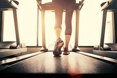 Corpo più basso alla parte delle gambe di funzionamento della ragazza di forma fisica sul machi corrente Fotografie Stock