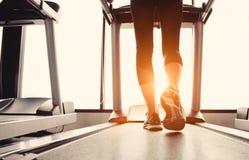 Corpo più basso alla parte delle gambe di funzionamento della ragazza di forma fisica sul machi corrente Immagine Stock Libera da Diritti