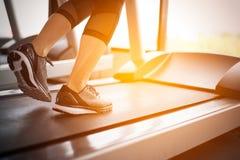 Corpo più basso alla parte delle gambe di funzionamento della ragazza di forma fisica sul machi corrente Immagine Stock