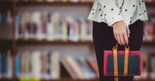 Corpo più basso dello studente di college contro lo scaffale per libri confuso Fotografia Stock Libera da Diritti