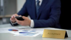 Corporate accountant in business suit typing message on phone, papers on table stock photo