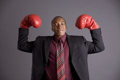 Corporate Battle. Business man dancing around in boxing gloves Stock Photography
