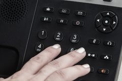 A close up woman hand dialing, a Black office IP Phone on a desk royalty free stock photos