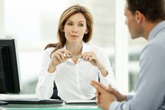 Corporate business executive woman listening to young businessman in office. Corporate business executive women listening to young businessman in office royalty free stock photo