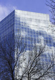 Corporate business glass building reflecting the sky and clouds Stock Photos
