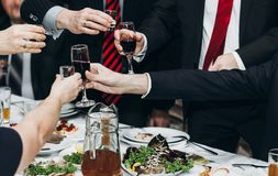 Corporate business man toasting at dinner party table hands close-up, wedding reception guests toast alcohol drinks in glasses. For newlyweds, happy people stock image
