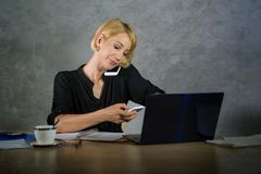 Corporate business portrait of young beautiful and busy woman with blonde hair working at office laptop computer desk talking and. Multitasking with mobile stock images