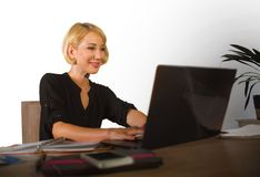 Corporate business portrait of young beautiful and happy woman with blonde hair smiling while working relaxed at office laptop com Royalty Free Stock Image
