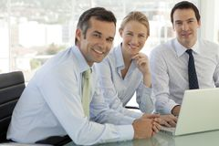 Corporate business teamwork - businessmen and woman working on laptop stock photography
