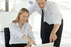 Corporate business teamwork - businessman working with woman on computer royalty free stock image