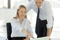 Corporate business teamwork - businessman working with woman on computer stock photography
