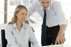 Corporate business teamwork - businessman working with woman on computer stock photo