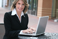 Corporate, Business Woman with Laptop Outdoors. Attractive corporate, business woman working on her laptop outdoors, in a city street Royalty Free Stock Photography