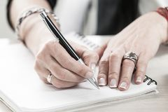 Corporate business, woman`s hands writing in a note pad royalty free stock photos