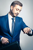 Corporate businessman. Handsome corporate businessman checking the time on his watch Stock Image