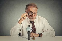 Corporate businessman looking through magnifying glass at employee Royalty Free Stock Image