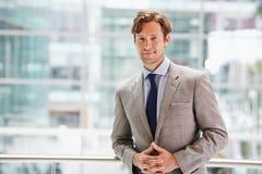 Corporate businessman in modern interior, waist up portrait Stock Photo