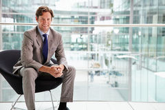 Corporate businessman sitting in modern interior Royalty Free Stock Image