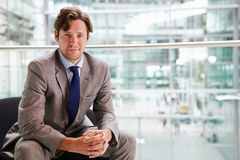 Corporate businessman sitting in modern interior, portrait Royalty Free Stock Image
