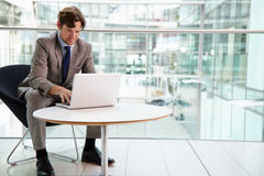 Corporate businessman using laptop computer, full length Royalty Free Stock Images