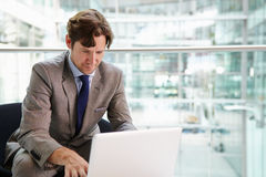 Corporate businessman using laptop computer, waist up Stock Photo
