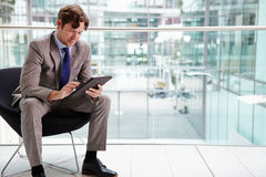 Corporate businessman using tablet computer, full length Stock Photo