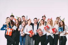 Corporate, celebration and holidays concept - happy team with gifts having fun birthday party. Corporate, celebration and holidays concept - happy team with royalty free stock photo