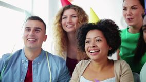 Happy team throwing confetti at office party. Corporate, celebration and holidays concept - happy team throwing confetti and serpentine at office party stock footage