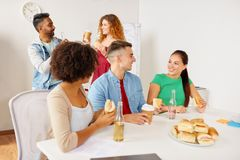 Happy friends or team eating at office Royalty Free Stock Photography