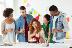 Team greeting colleague at office birthday party Stock Photos