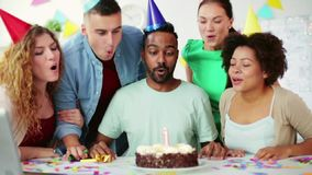 Corporate team celebrating one year anniversary. Corporate, celebration and people concept - happy team celebrating one year anniversary and blowing candle out stock footage