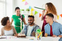 Team greeting colleague at office birthday party. Corporate, celebration and people concept - happy team with firework on birthday cake and non-alcoholic drinks Royalty Free Stock Images