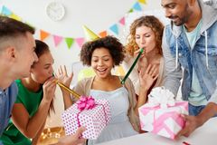 Team greeting colleague at office birthday party. Corporate, celebration and people concept - happy team with gifts greeting female colleague at office birthday Stock Images