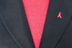 Corporate charity fundraising for AIDS. Closeup of woman in business suit wearing AIDS badge on lapel. Fundraising / charity concept Royalty Free Stock Images