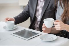 Corporate coffee break! Young businesspeople sitting at the tabl Stock Photography