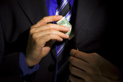 Corporate Corruption. Businessman putting bundle of dollars to his jacket pocket Stock Photography