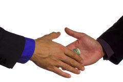 Corporate Corruption. Businessmen shaking hands with bundle of dollars Royalty Free Stock Photography