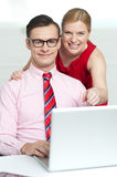 Corporate couple enjoying videos on laptop Royalty Free Stock Image