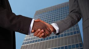 Corporate Deal. This is an image of two business hands performing a handshake, with a corporate building in the background Stock Images