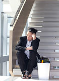 Corporate Downsizing. Downsizing, sad business woman Sitting on Stairs Royalty Free Stock Photo