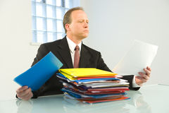 Corporate employee with files. Business man reviewing stack of files Royalty Free Stock Photos