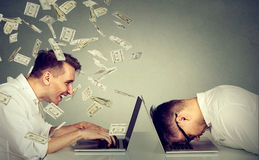 Corporate employee income compensation economy concept. Stressed desperate burnout man resting sleeping on laptop sitting next to professional man under money Royalty Free Stock Image