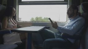 Man and woman or coworkers enjoying conversation while they using their gadget on train compartment commuting to office. Corporate employees man and woman or stock footage
