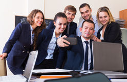 Corporate employees photoshooting together. Using the mobile phone Stock Image
