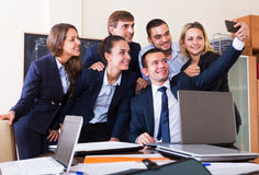 Corporate employees photoshooting together. Using a mobile phone Royalty Free Stock Image