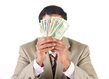 Corporate executive covering face with  currency. Rich businessman hiding behind american dollars Stock Image
