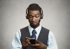 Corporate executive with headphones  holding mobile phone Stock Photo