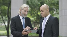 Corporate executives discussing business using digital tablet. Caucasian and latino corporate executives discussing business using digital tablet royalty free stock photography