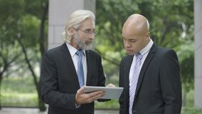 Corporate executives discussing business using digital tablet. Caucasian and latino corporate executives discussing business using digital tablet royalty free stock photos