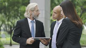 Corporate executives discussing business using digital tablet stock photos